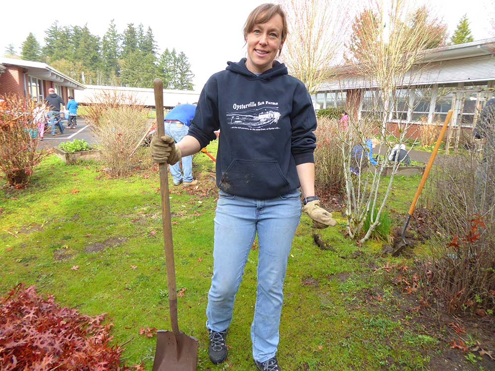 Adult helper poses with a shovel in the garden